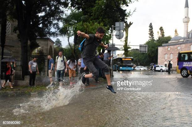 A man jumps in a flooded street after a heavy downpour of rain and hail at Besiktas near Istanbul on July 27 2017 / AFP PHOTO / Bulent KILIC