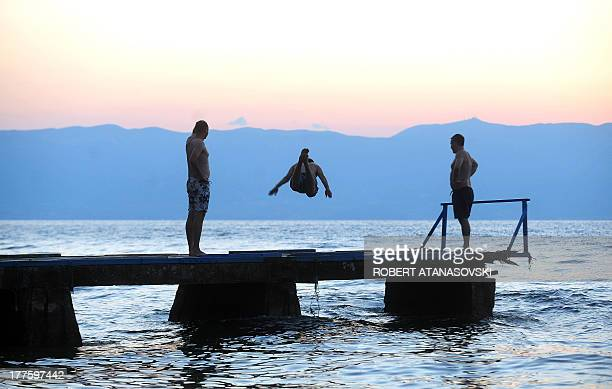 A man jumps in the Ohrid Lake in Ohrid Macedonia at sunset on August 24 2013 Hot and sunny weather in Macedonia forced residents of the Balkan...