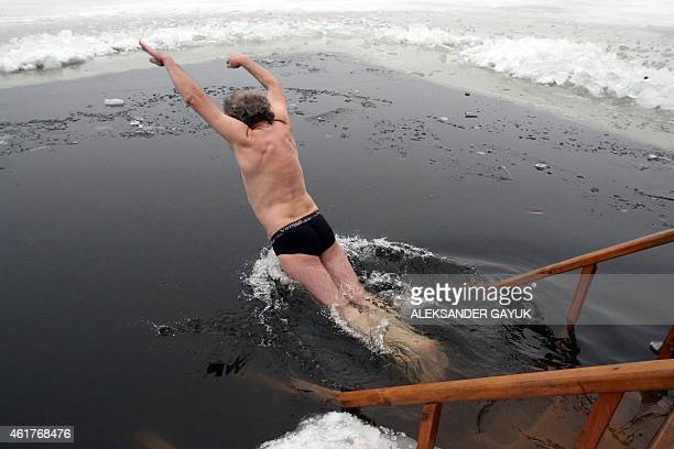 A man jumps into icy waters of a pond on January 19 2015 during celebrations for the Epiphany in the eastern Ukrainian city of Donetsk Among Orthodox...