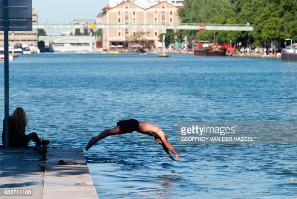 A man jumps into the water at the Bassin de la Villette in Paris on May 26 2017 Amateurs will be able to bathe at the La Villette canal bassin and on...