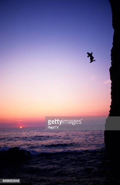a man jumps of a huge sea cliff at sunset. - leap of faith stock photos and pictures