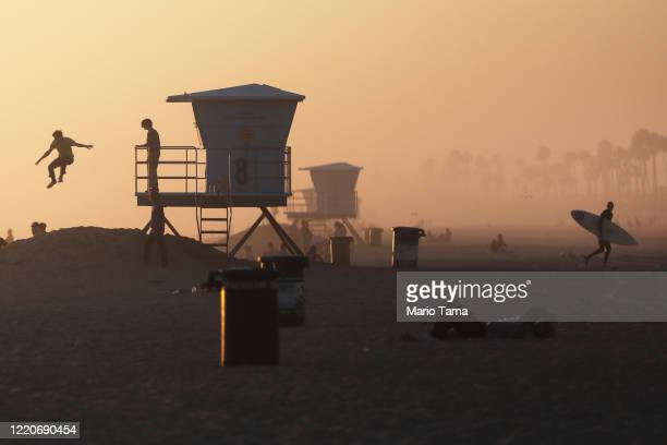A man jumps off a lifeguard station as a surfer leaves Huntington Beach which remains open amid the coronavirus pandemic on April 23 2020 in...