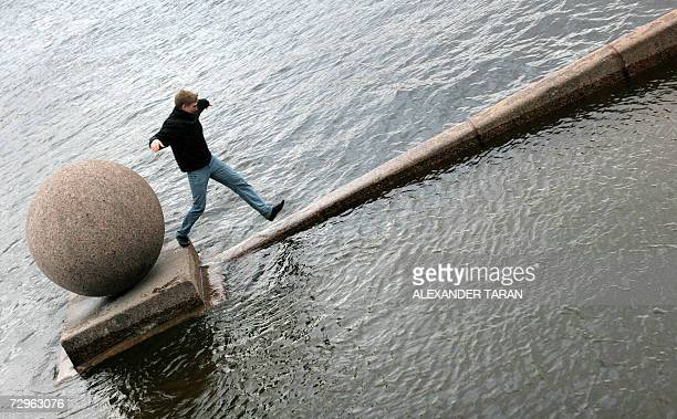 A man jumps on a flooded embankment of Neva river in StPetersburg 10 January 2007 The historic centre of Saint Petersburg was under threat 10 January...