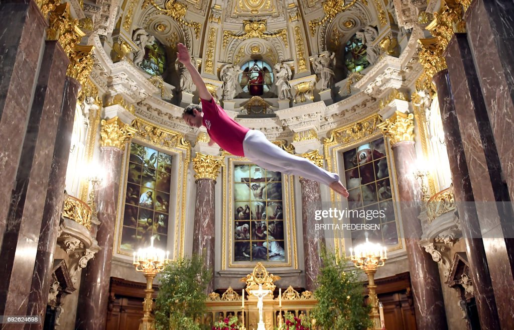 TOPSHOT - A man jumps on the trampoline during a service in the Berlin Cathedral on June 5, 2017 in Berlin. / AFP PHOTO / dpa / Britta Pedersen / Germany OUT