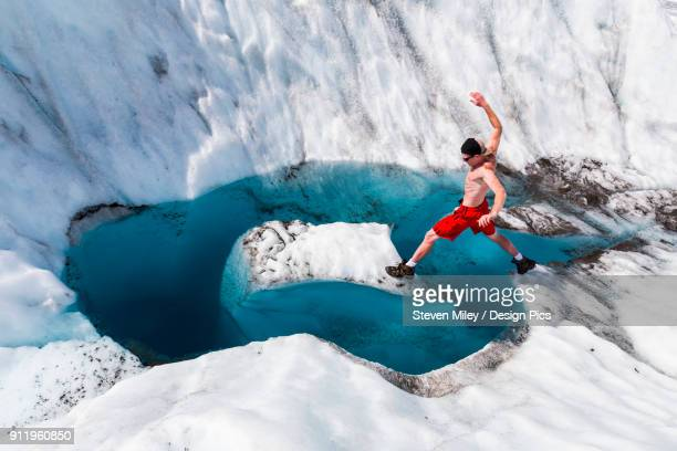a man jumps onto an island of ice on root glacier in wrangell-st. elias national park - halbbekleidet stock-fotos und bilder