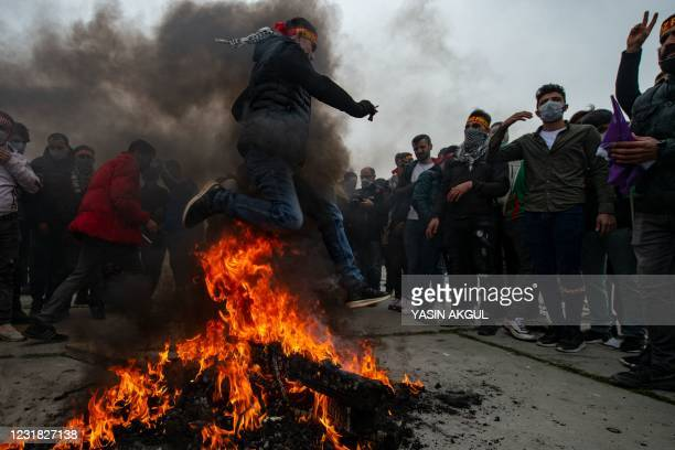 Man jumps over a bonfire during a Kurdish celebration of Nowruz, the Persian New Year, in Istanbul on March 20, 2021.
