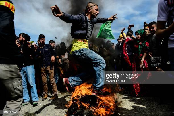 TOPSHOT A man jumps over a bonfire during a Kurdish celebration of Nowruz the Persian calendar New Year in Istanbul on March 21 2018