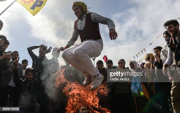 A man jumps over a bonfire during a Kurdish celebration of Nowruz the Persian calendar New Year in Istanbul on March 21 2018 / AFP PHOTO / YASIN AKGUL