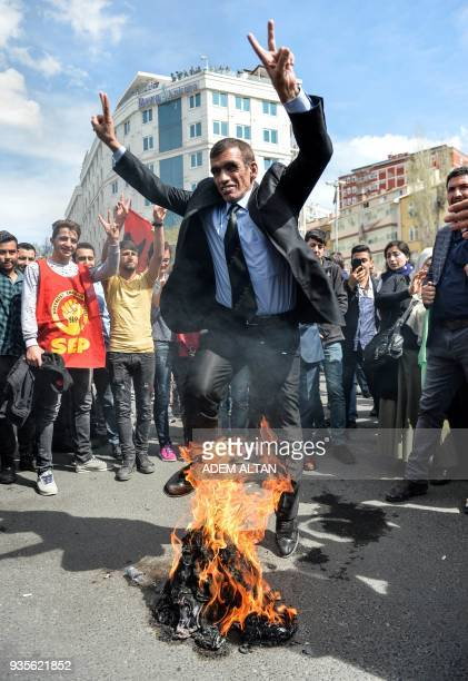 A man jumps over a bonfire during a Kurdish celebration of Nowruz the Persian calendar New Year in Ankara on March 21 2018 / AFP PHOTO / ADEM ALTAN