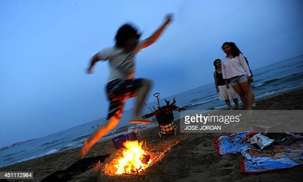 A man jumps over a bonfire during the annual San Juan celebrations on a beach in Alicante on June 23 2014 Fires are lit throughout Spain on the Eve...