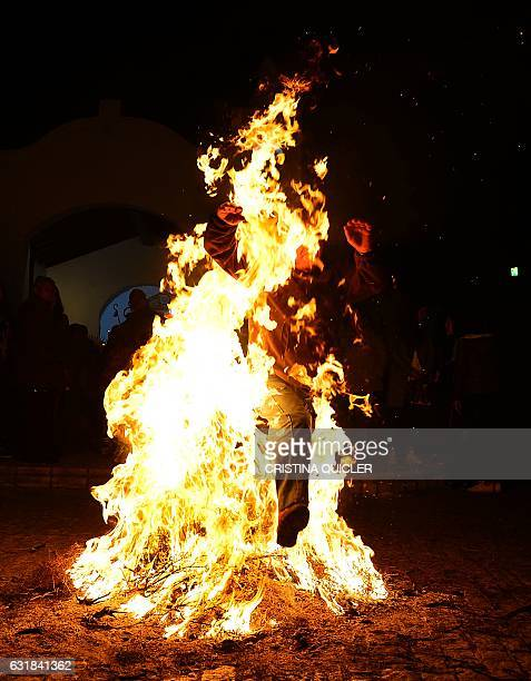 A man jumps over a bonfire during the celebrations of the traditional religious festival Luminarias in honour of San Antonio Abad patron saint of...
