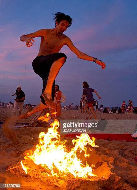 A man jumps over a bonfire during the traditional San Juan celebrations on a beach of Valencia on June 23 2013 Fires are lit throughout Spain on the...