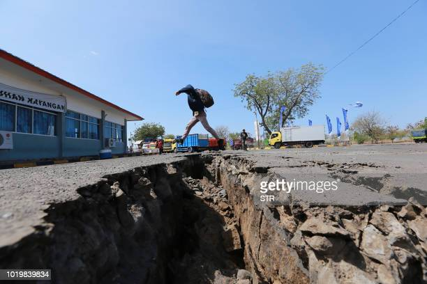TOPSHOT A man jumps over a crack in the ground in Mataram on Indonesia's Lombok island on August 20 2018 after a series of earthquakes were recorded...