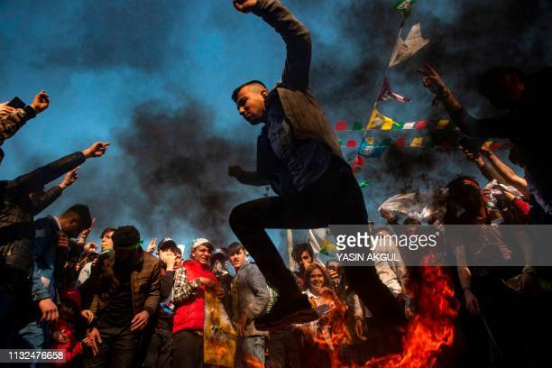 A man jumps over a fire as thousands of supporters of Turkey's main proKurdish Peoples' Democratic Party gather to celebrate the Kurdish New Year...