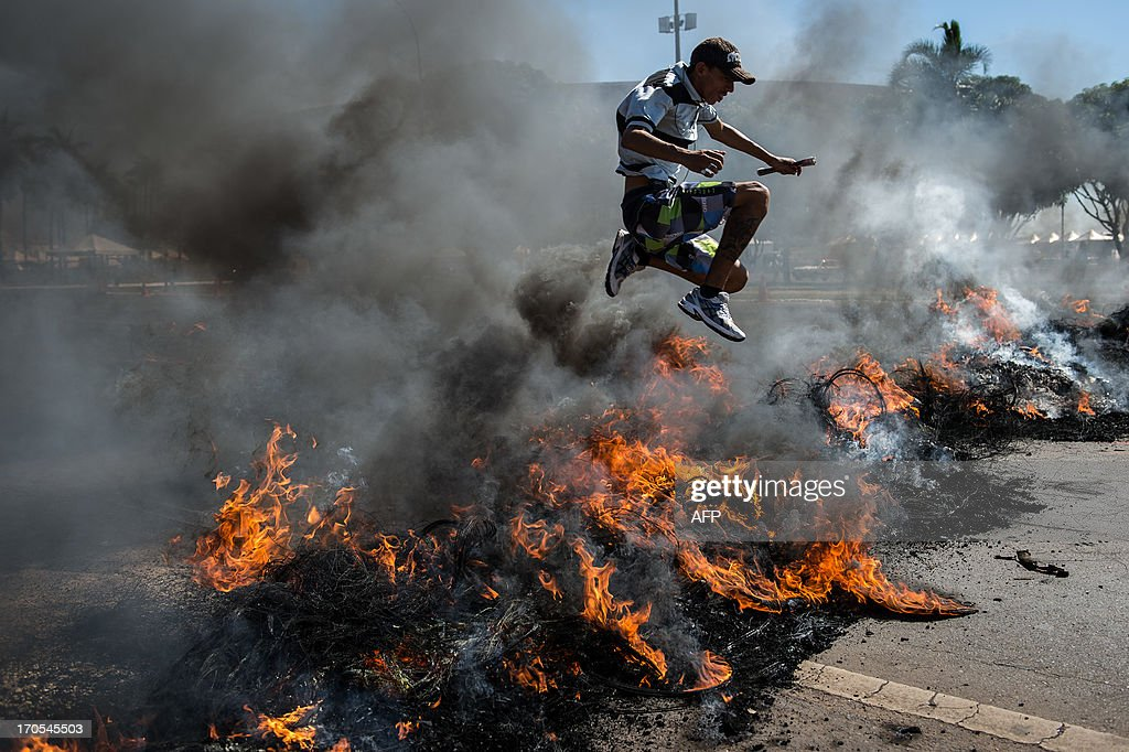 A man jumps over burning tyres set on fire by people who also block access to Brasilia's Mane Garrincha, one of the six host stadiums for the upcoming Confederations Cup, to protest in part against the government's policy of the expenditure for the 2014 FIFA World Cup, on June 14, 2013. A police spokesman said the protest was organized by the Homeless Workers Movement (MTST) which is campaigning to reduce Brazil's housing shortage by staging squatters' occupations in abandoned government buildings. Brazil faces Japan Saturday at Mane Garrincha in the opening game of the two-week Confederations Cup, a dry run for next year's World Cup.