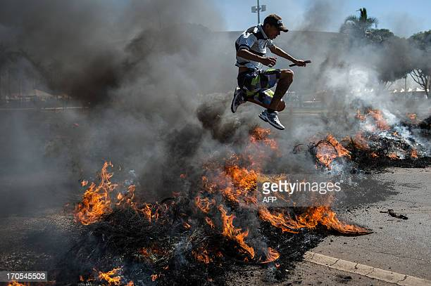 A man jumps over burning tyres set on fire by people who also block access to Brasilia's Mane Garrincha one of the six host stadiums for the upcoming...