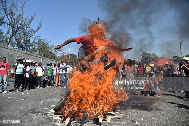 TOPSHOT A man jumps over the fire while perform a voodoo ceremony prior a protest for the streets of PortauPrince on January 19 2016 Demonstrators...