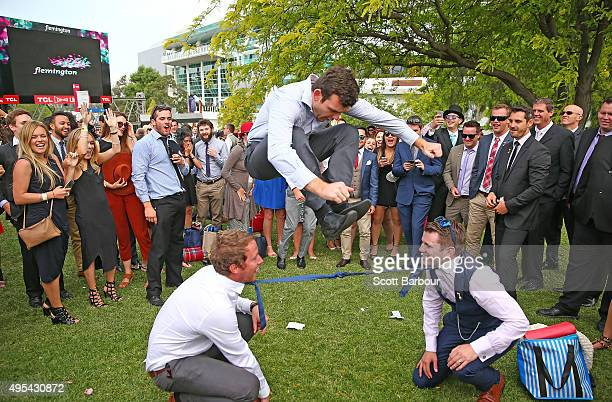 A man jumps over two racegoers who have their ties tied together as racegoers play a game of Limbo following 2015 Melbourne Cup Day at Flemington...