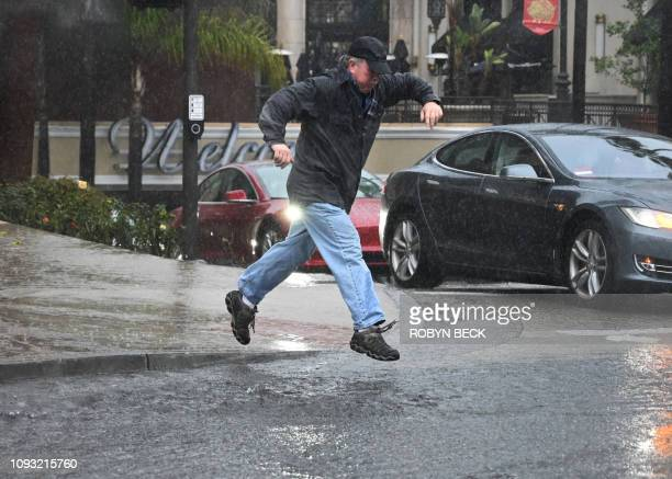 A man jumps over water flooding a street in Glendale California on February 2 2019 Southern California is enduring three backtoback storms bringing...