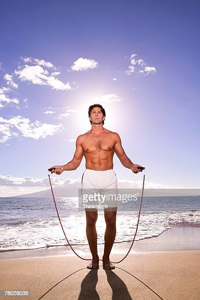 A man jumps rope on the beach with the sun behind him.