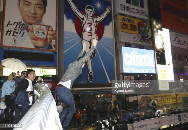 A man jumps to a river in Osaka's Dotonbori entertainment district in celebration of the start of Reiwa Japan's new imperial era in the small hours...