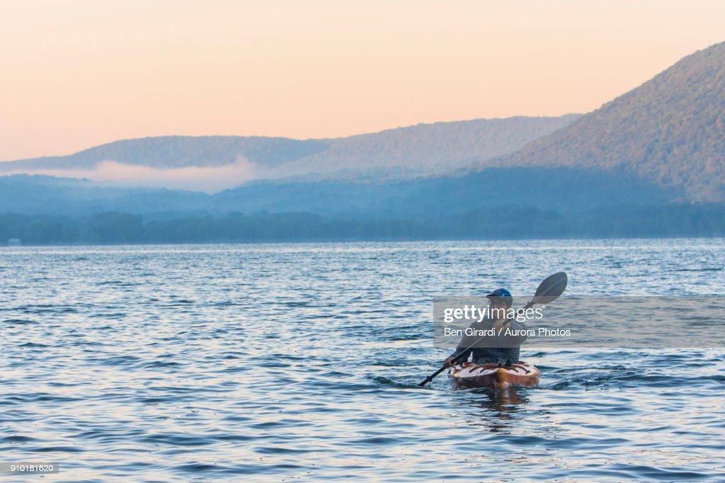 Man kayaking at sunrise on Skaneateles Lake, Skaneateles, New York State, USA : Stock Photo