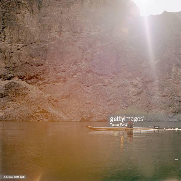 Man kayaking in calm waters, sunset