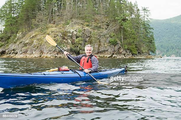 Man kayaking in fjord