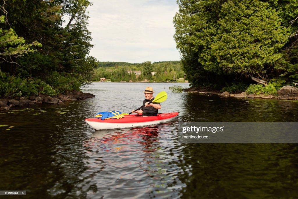 50 + man kayaking on a lake. : Stock Photo