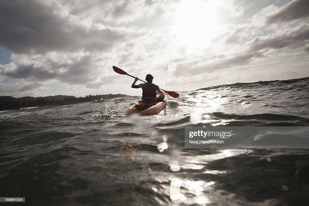A man kayaks in the ocean : Stock Photo