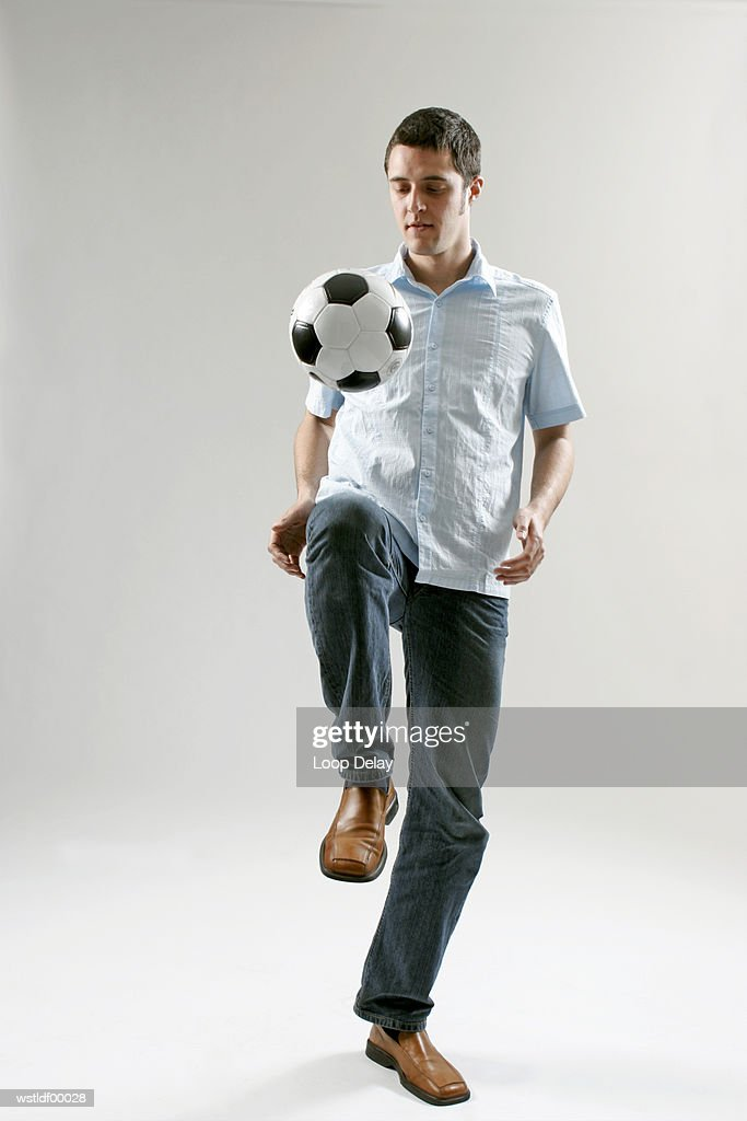 Man keeping football in the air with his knee : Stock Photo