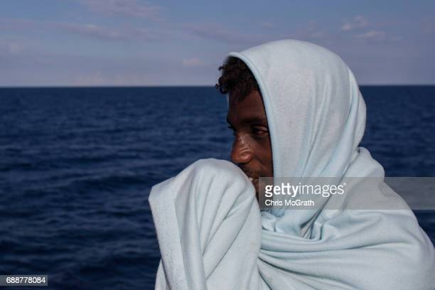 A man keeps warm wrapped in a blanket on board the Migrant Offshore Aid Station 'Phoenix' vessel on May 26 2017 off Crotone Italy The refugees and...