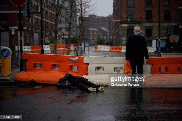 Man keeps watch over a man lying on the ground as they wait for emergency services during lockdown three on January 13, 2021 in Manchester, United...