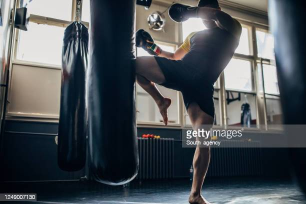 man kick boxer training alone in gym - mixed martial arts stock pictures, royalty-free photos & images
