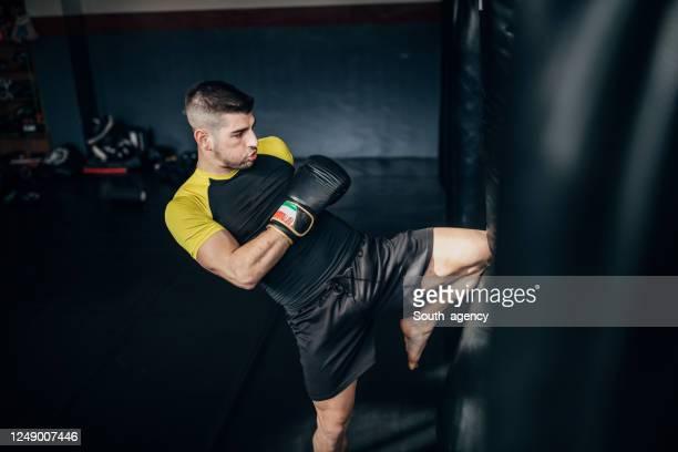 mann kick boxer training allein in der turnhalle - free fight stock-fotos und bilder