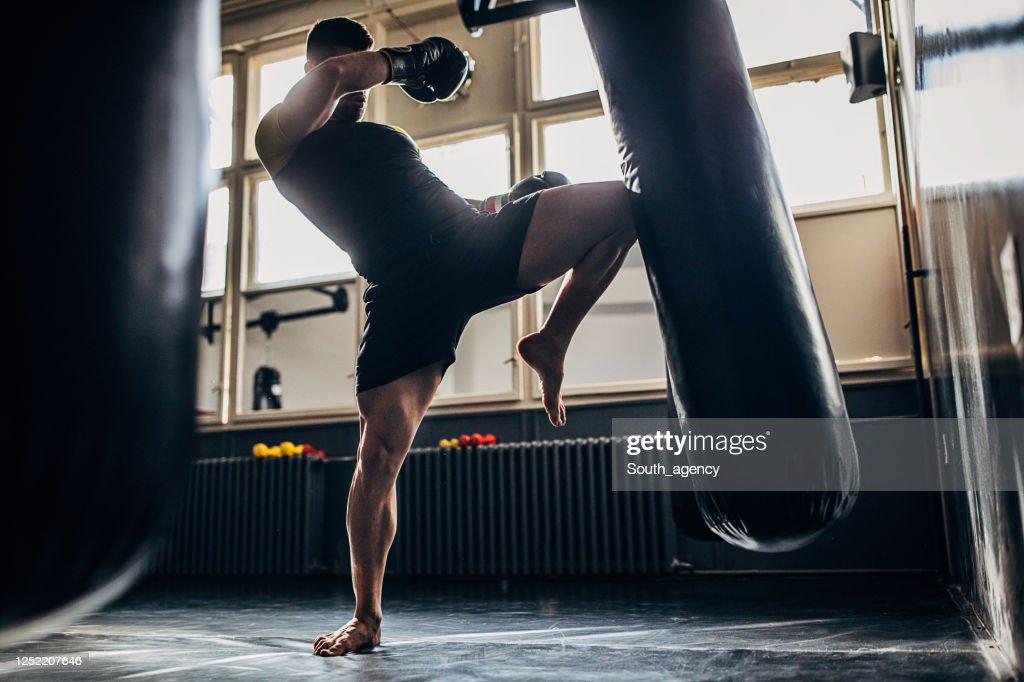 Homem chuta boxeador treinando sozinho na academia : Foto de stock