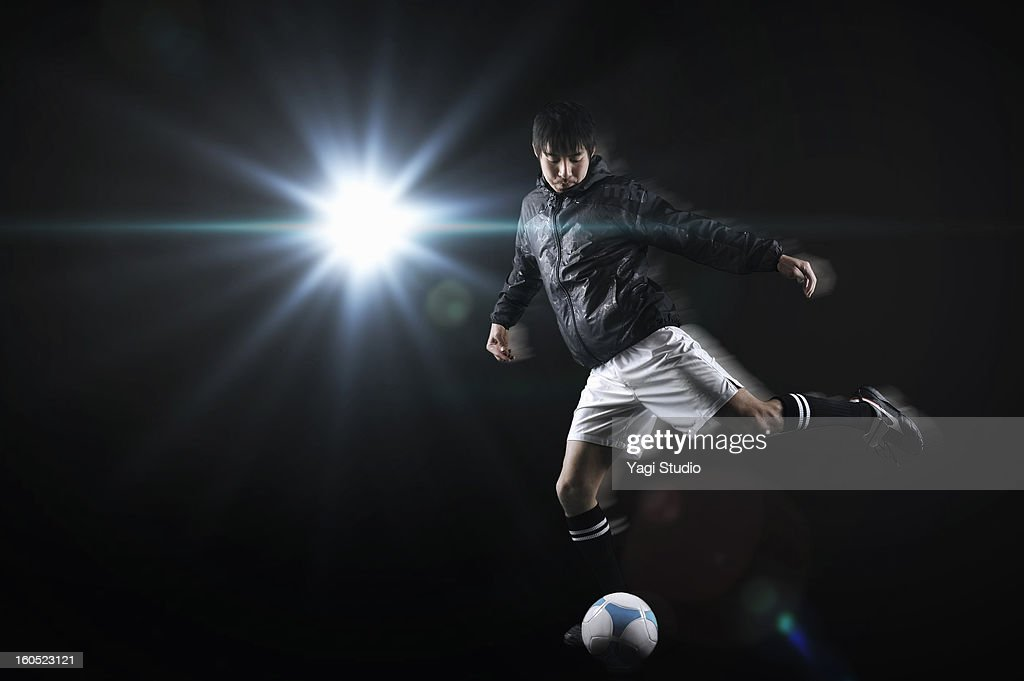 Man kicking a soccer ball : Stock Photo