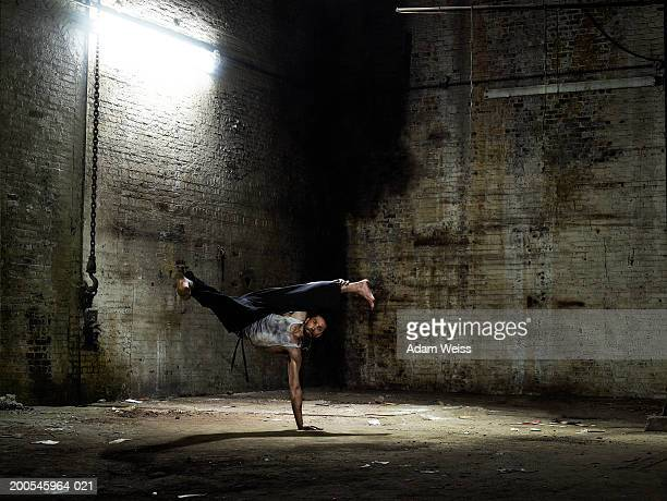 Man kicking, balancing on one hand in empty industrial space