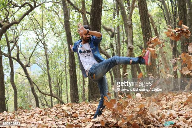 man kicking dry leaves in forest - punt kick stock pictures, royalty-free photos & images