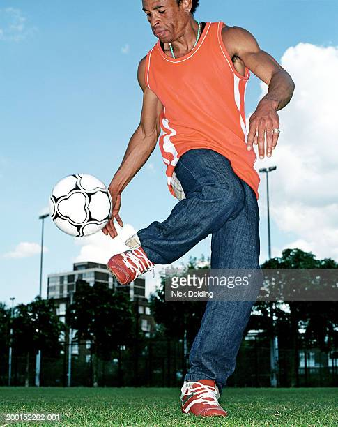 Man kicking football outdoors, low angle view