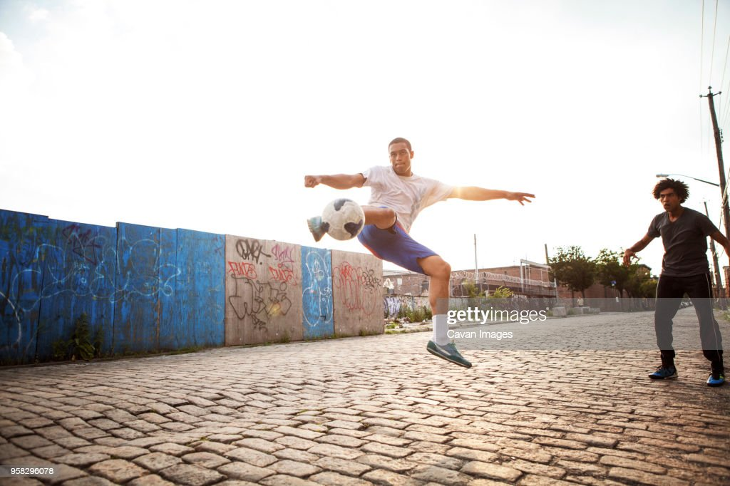 Man kicking soccer ball while friend looking at street : Stock Photo