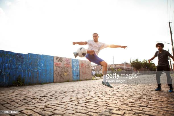 man kicking soccer ball while friend looking at street - cavan images foto e immagini stock