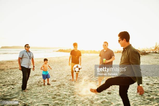 Man kicking soccer ball with friends on beach at sunset