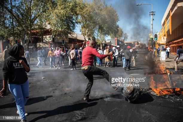 TOPSHOT A man kicks a burning piece of furniture during a riot in the Johannesburg suburb of Turffontein on September 2 2019 as angry protesters loot...