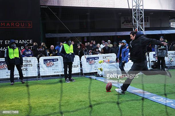 A man kicks a football into a net as fans gather along Broadway in Times Square which has temporarily been renamed Super Bowl Boulevard as the city...