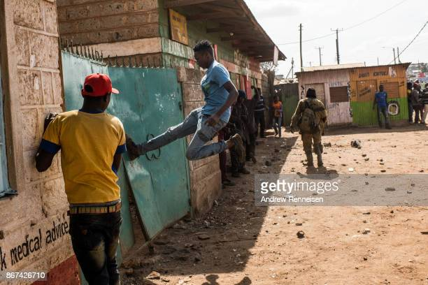 A man kicks a gate in an attempt to loot a residential compound in the Kawangware slum on October 28 2017 in Nairobi Kenya Protests continued in...
