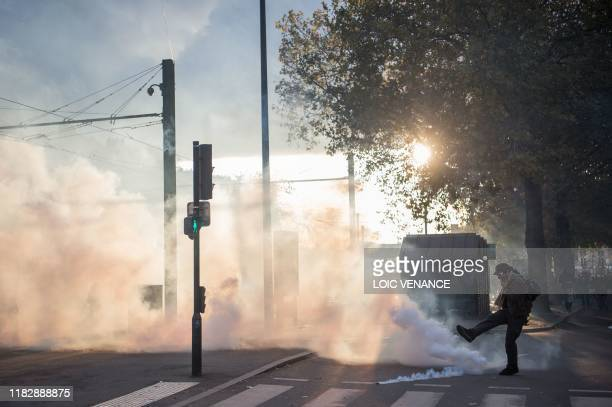 A man kicks a tear gas canister during a demonstration marking the first anniversary of the yellow vest movement on November 16 in Nantes western...