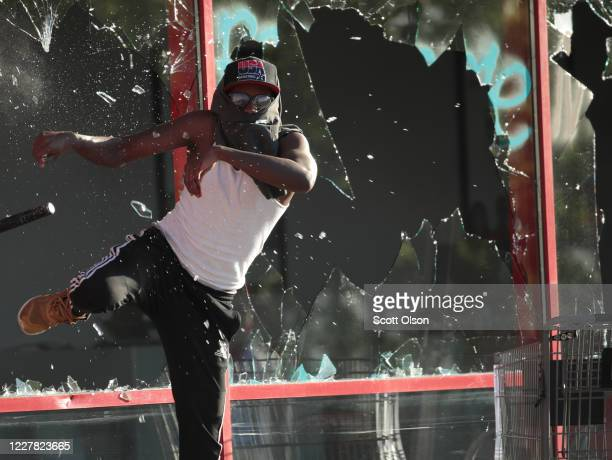 Man kicks out a store front window during a protest on May 28, 2020 in St. Paul, Minnesota. Today marks the third day of ongoing protests after the...