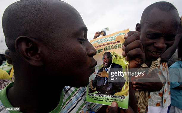 A man kisses a book written in honor of exIvory Coast strongman Laurent Gbagbo during a demonstration by Gbagbo supporters in the Koumassi district...