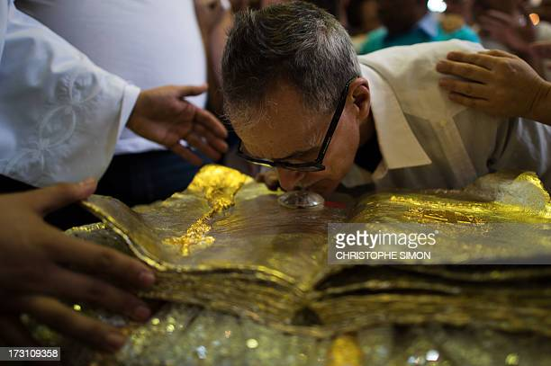 A man kisses a relic after a mass officiated by Cardinal Stanislaw Rylko to celebrate the arrival in Brazil of the relics of blessed John Paul II at...